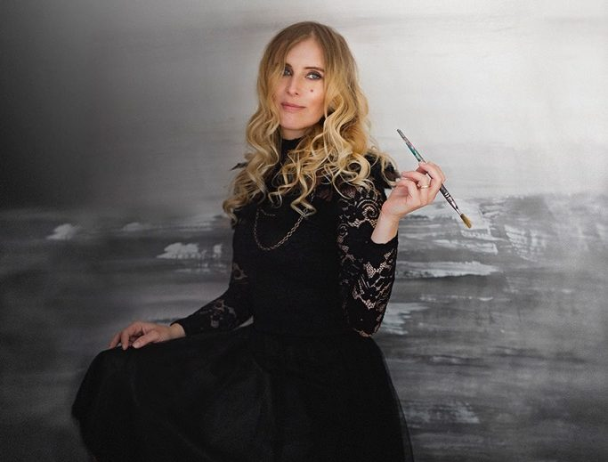 Portrait of Canadian Artist Nathalie Van sitting in front of a grey seascape holding a paint brush to illustrate her Artist Bio