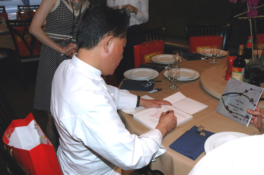 TV Chef Martin Yan signing his cook book to artist Nathalie Van