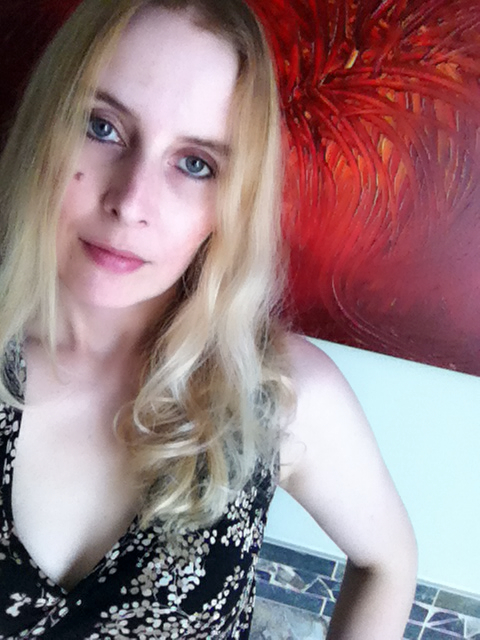 Photograph of Artist Nathalie Van with a red abstract painting in the background