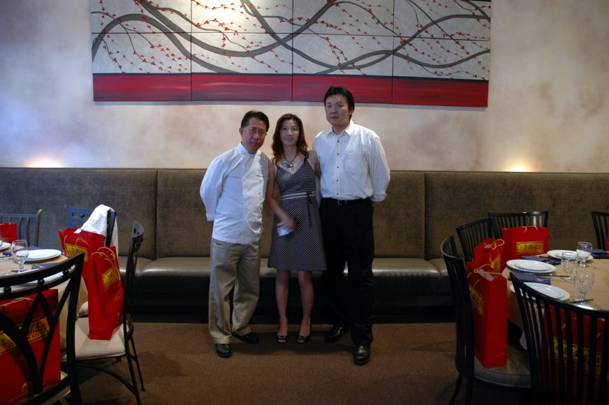 Martin Yan and Francis Koo and his wife in front of a huge commissioned cherry blossom painting by nathalie van